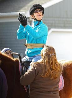 Hopkinton, MA 012812 Twenty-year old Stephanie Hart (cq), who suffers from cerebral palsy, claps in approval as she rides a horse at the Equine Parts Inc a.k.a. Therapeutic Equestrian Center in Hopkinton on Saturday January 28, 2012 during a therapeutic ride. (on the left of froam is instructor Nicole Majkut (Cq) w glasses, and back to camera volunteer Lori Mackay (cq) of Medway.) (Essdras M Suarez/ Globe Staff)/ NOWK